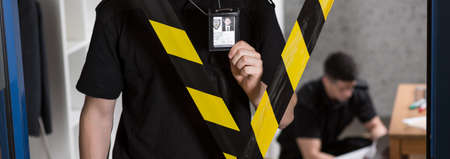 police tape: Panorama of uniformed policeman standing behind police tape