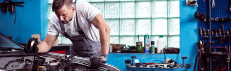 mecanico: Hombre que repara un coche en el garaje Foto de archivo