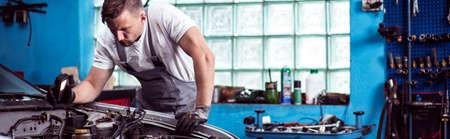 Man repareren van een auto in de garage