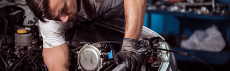 Close-up of motor mechanic repairing car engine 스톡 콘텐츠