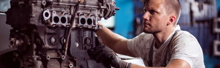riparatore: Repairer fixing car engine in the workshop