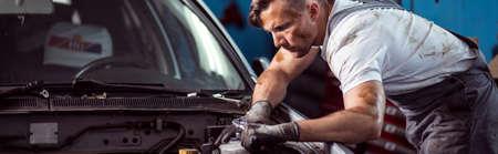 car repair shop: Young auto mechanic working in car repair shop