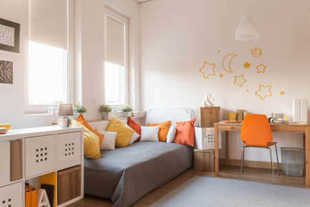 Yellow and orange accessories in modern teen room