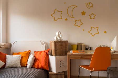 niño durmiendo: Cojines anaranjados y una silla en la habitación de adolescente Foto de archivo