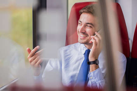 deal making: Picture of businessman in train making deal by phone call Stock Photo