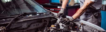 Close-up of car mechanic fixing automotive engine 스톡 콘텐츠