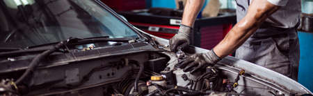automotive repair: Close-up of car mechanic fixing automotive engine Stock Photo