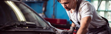 repairer: Auto mechanic fixing the car in repair shop Stock Photo
