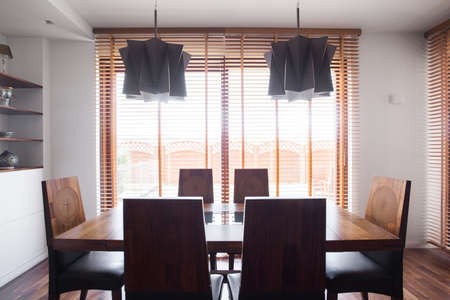 wood blinds: Image of solid simple design wooden dining table and chairs Stock Photo