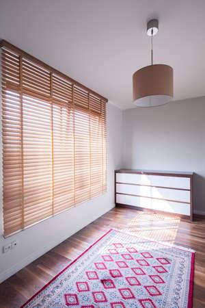 ブラインド窓が大きくてシンプルな部屋のインテリアの写真