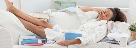 house robe: Panorama of lazy sleepy girl lying on sofa with books