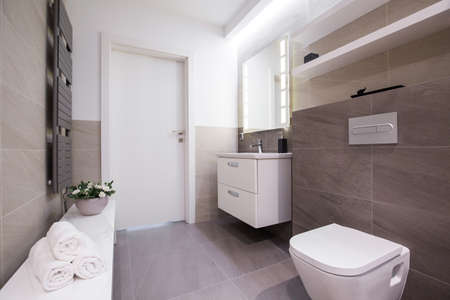 bathroom tile: Image of spacious light bathroom with grey tiling