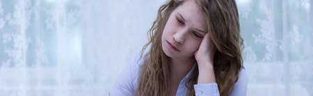 persona deprimida: Image of sad young woman with headache