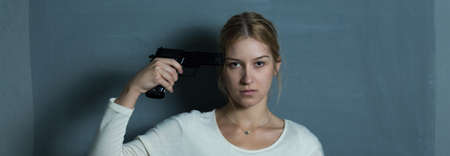 women with guns: Young and pretty woman is thinking about suicide Stock Photo
