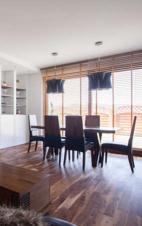 dining room: Picture of stylish dining area with big blind windows Stock Photo