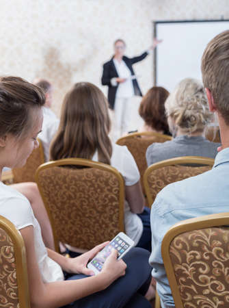listener: Photo of listener with cellphone during dull presentation