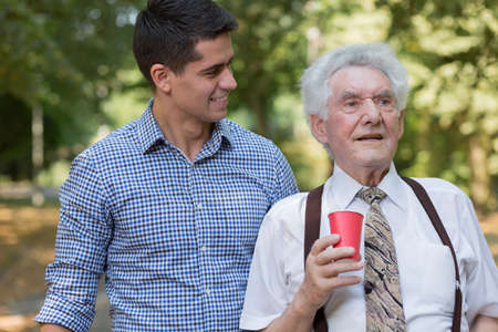 senescence: Photo of handsome male volunteer supporting old man
