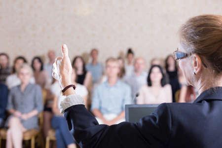 Foto van de docent het geven van vloer tot luisteraar tijdens panel