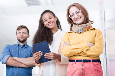 company director: Photo of female company director and two young interns Stock Photo