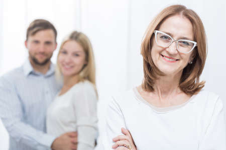 felicity: Smiling mother-in-law with happy family in background Stock Photo