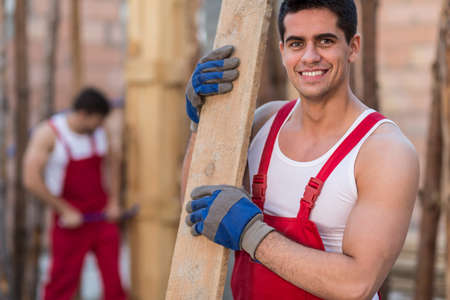 young worker: Smiling building worker holding timber at building site