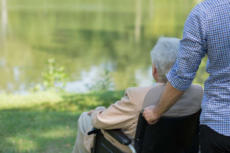 Photo of elderly man on wheelchair and his private carer