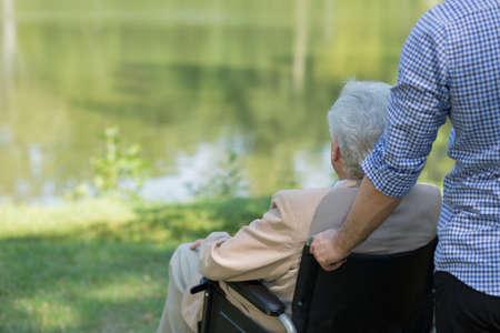 Foto van de oudere man op de rolstoel en zijn prive-verzorger