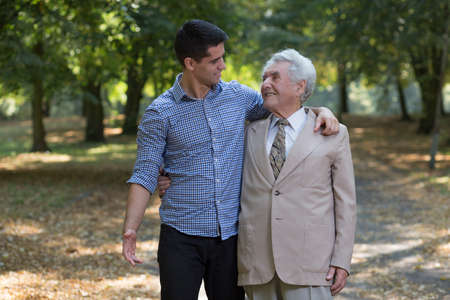 Photo of happy father and son walking in park