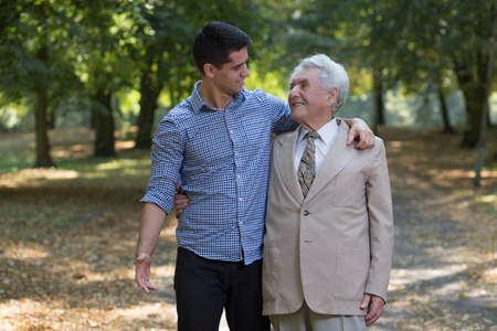 Foto van de gelukkige vader en zoon lopen in het park