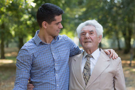 leisure time: Image of caring grandson and his grandfather outdoor Stock Photo