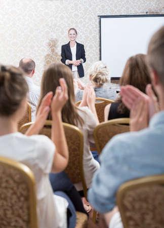 講義の後の女性教授の拍手の観客の写真