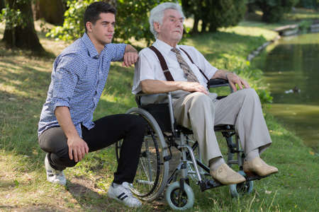 senility: Photo of disabled retired person and male carer outdoor