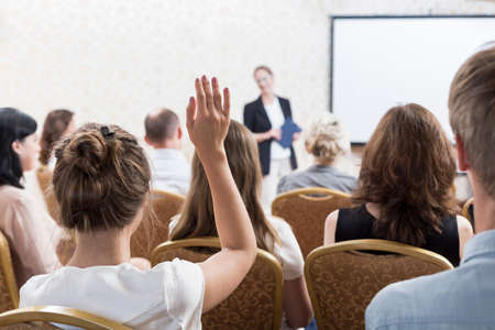 professor: Photo of listener raising hand to ask question during seminar