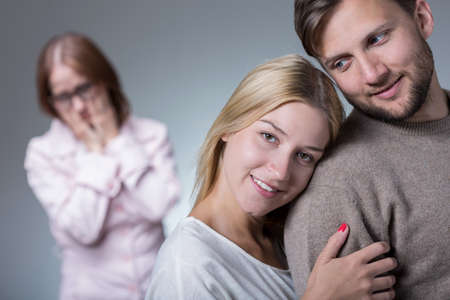 difficult: Happy young couple and difficult jealous mother-in-law Stock Photo