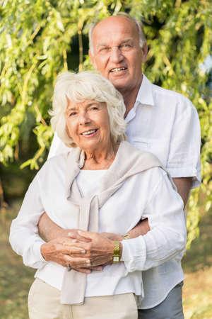 tenderly: Senior couple is cuddling tenderly in park