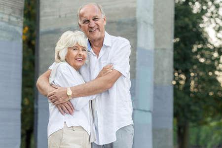 Very happy elder people hugging each other