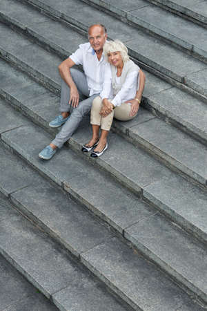 married couples: Happy senior marriage sitting on concrete stairs