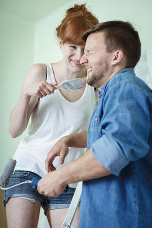 redecorating: Happy couple redecorating house and painting walls Stock Photo