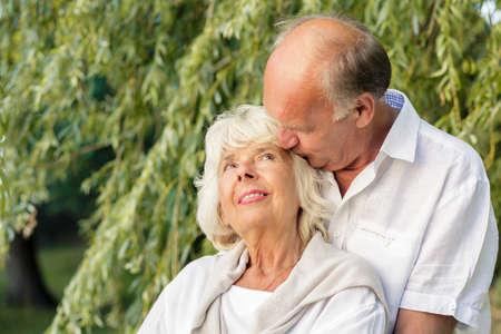 tenderly: Elder couple hugging tenderly in city park