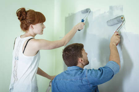 redecorating: Couple redecorating house and painting wall together Stock Photo