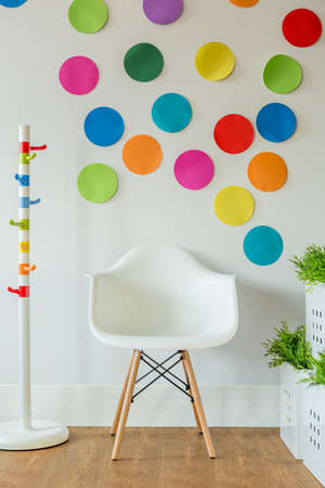childs: White chair and color spots on wall in childs room Stock Photo