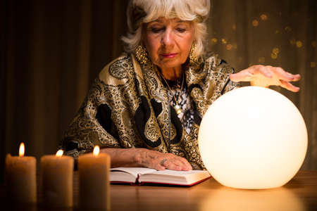 spirit medium: Old fortune teller is learning how to use crystal ball Stock Photo