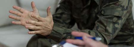 Soldado en uniforme militar verde - de cerca de las manos