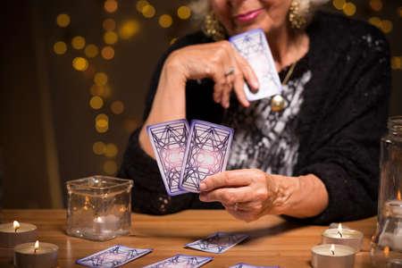 옛 점쟁이가 카드를보고있다.