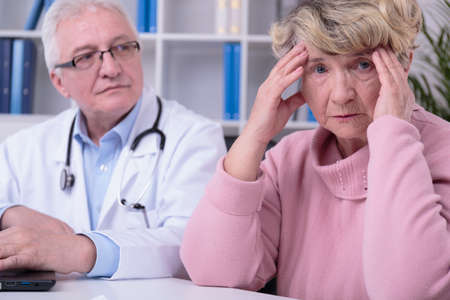 malady: Elder woman is worried because of her malady Stock Photo