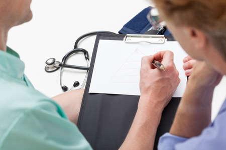 consulta médica: Doctor que discute con el paciente durante la consulta médica Foto de archivo