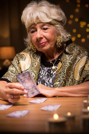 enchantment: Old fortune teller sees something good in cards