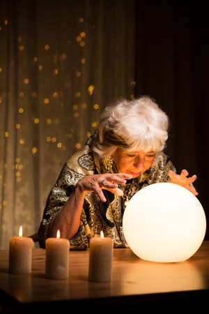 witchery: Old fortune teller has a contact with spirits Stock Photo