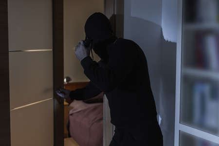 housebreaking: Male criminal in balaclava and black clothes Stock Photo