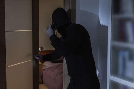 Mannelijke misdadiger in balaclava en zwarte kleren